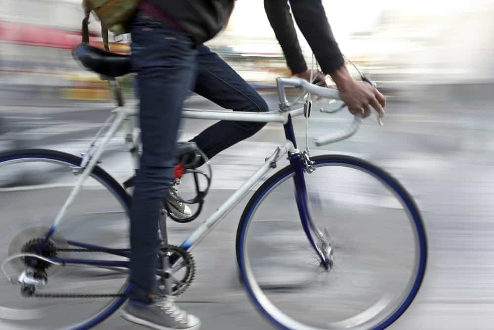 A close look at a city cyclist heading to work on a single speed bike.